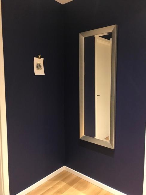 Een hal met een spiegel op een blauwe muur