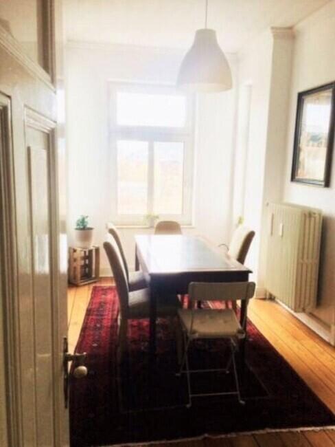woonkamer met eettafel en grote kast
