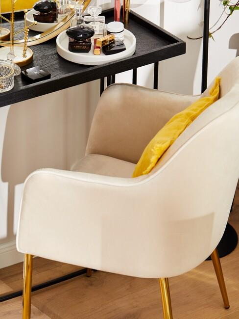 champagne-kleur stoel met gouden poten en geel kussen