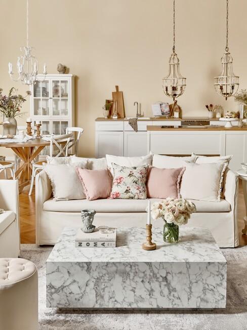 champagne kleur muur met witte bank en marmere salontafel