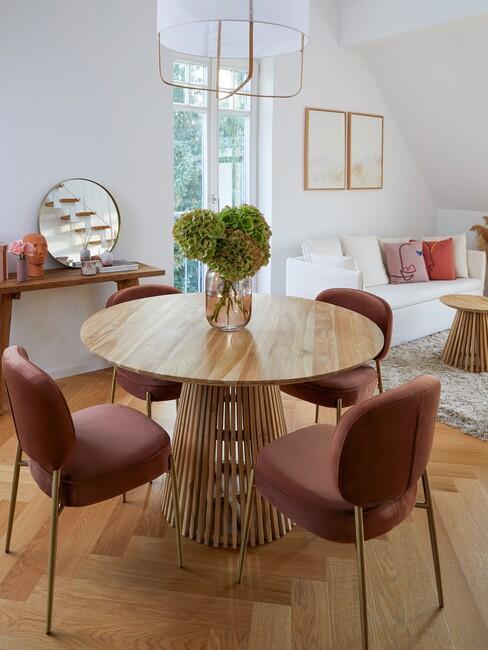 Ronde eettafel met roze stoelen en gouden spiegel