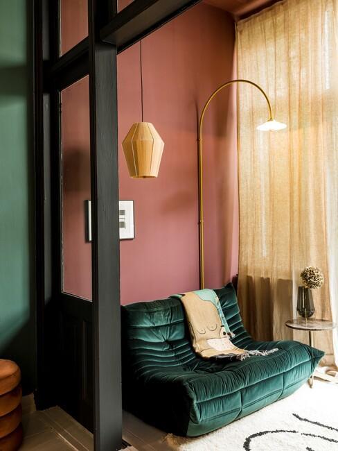 Roze muur met een groene bank en gouden lamp
