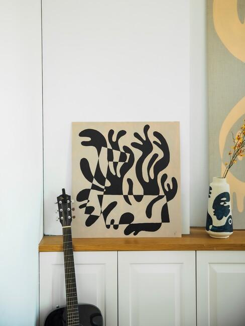 Kunstwerk op witte kast en gitaar