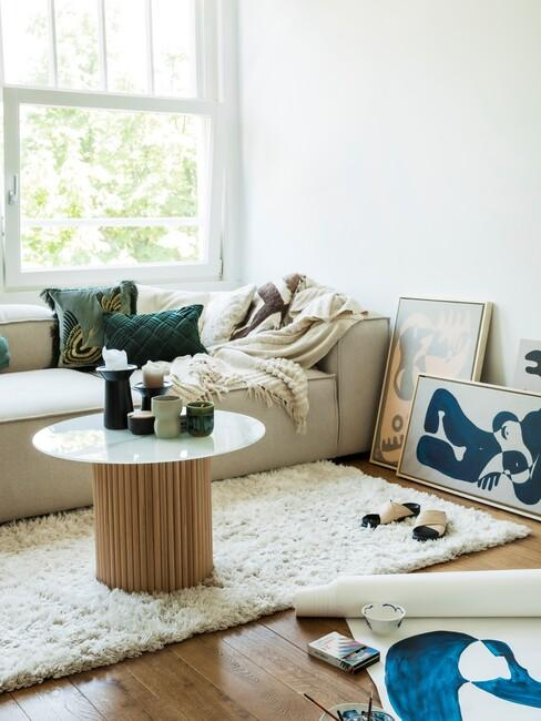 Beige bank met ronde houten salontafel