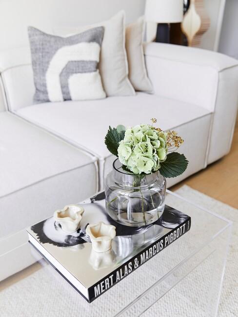Beige bank met een koffieboek op een glazen salontafel
