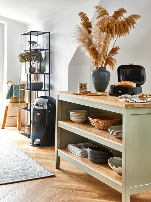 Zbliżenie na poziomą drewnianą szafkę w kuchni oraz metalową szafkę