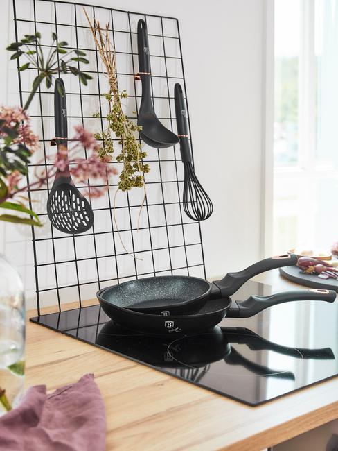 Zbliżenie na kuchnię indukcyjną z patelnią oraz organizerem na akcesoria kuchenne