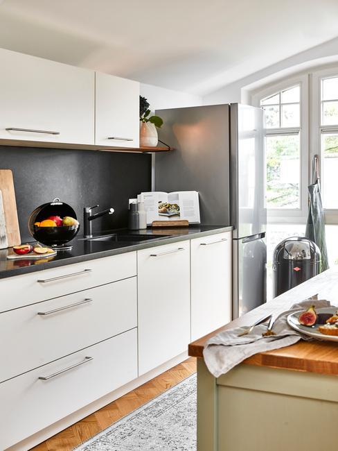 Kuchnia z szara ścianą, białymi frontami szafek oraz drewnianą wyspą kuchenną