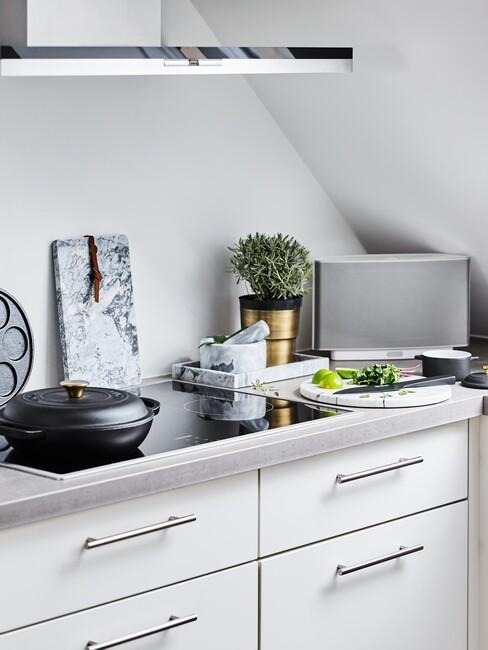 Kuchnia na poddaszku z białymi frontami szafek oraz akcesoriami