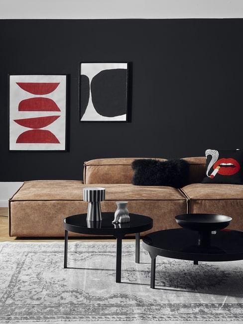 Grafiki na tle czarnej ściany i skórzana sofa w salonie