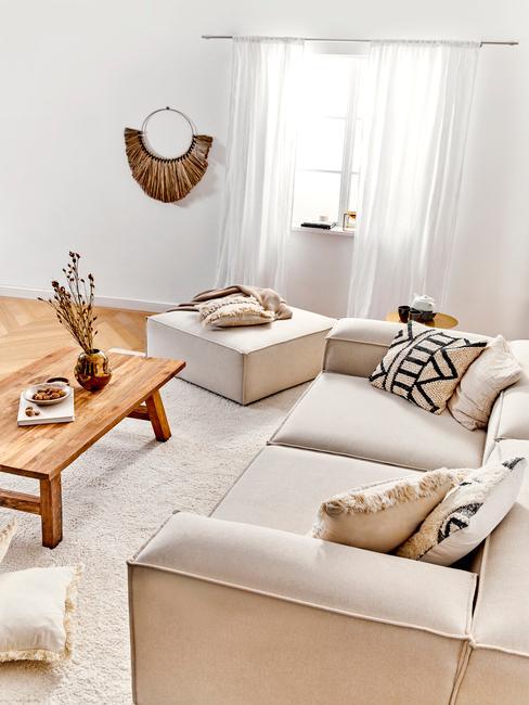 Jasny salon z drewnianym stoliczkiem kawowym, białą sofa z poduszkami o geometrycznych wzorach, pufem oraz białym dywanem