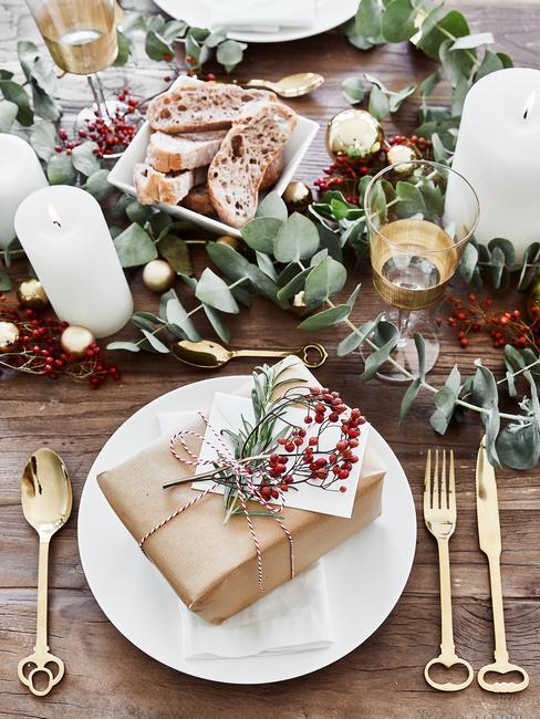 Drewniany stół w girlandą z eukaliptusa, białą zastawą, świecami oraz prezentem na talerzu