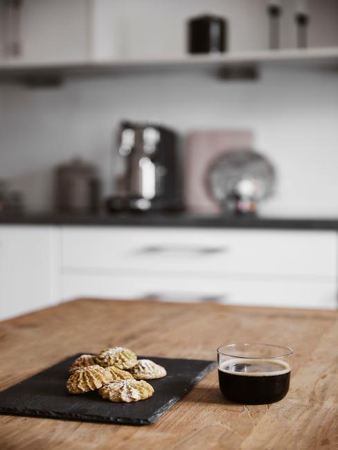 Szklana filiżanka z espresso na drewnianej wyspie kuchennej obok deski z ciastkami