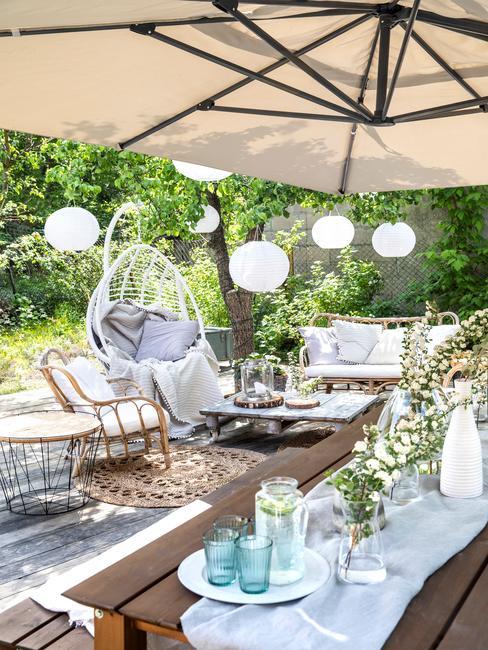 Fragment ogrodu w stylu boho z huśtawką, meblami ogrodowymi oraz parasolem