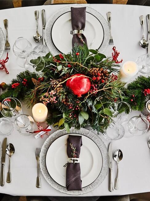 Owalny stół z białym obrusem, białą zastawą oraz stroikiem świątecznym