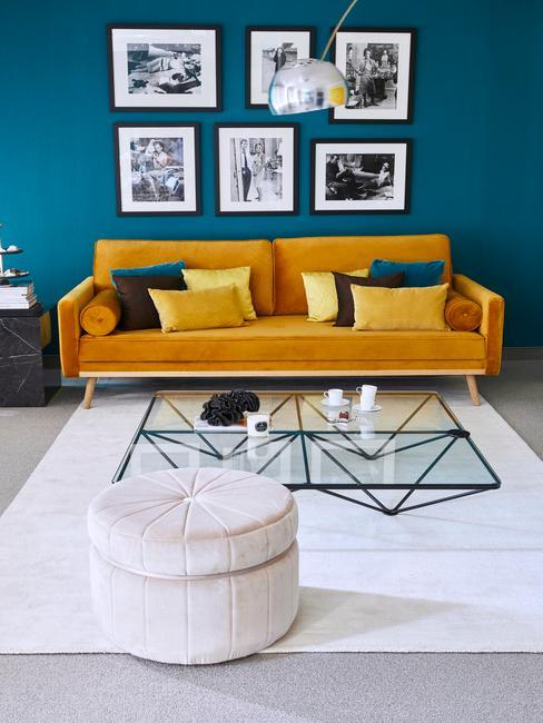Salon z niebieską ścianą oraz pomarańczową sofą