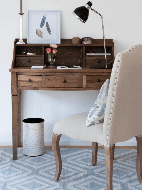 Fragment salonu w stylu rustykalnym z drewnianym sekretarzykiem oraz kremowym krzesłem