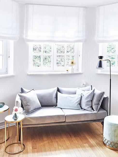 Kącik pod oknem z małą sofą z szarego aksamitu