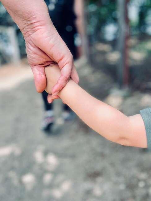 Ręka starszje osoby (babci) trzymając ręckę dziecka