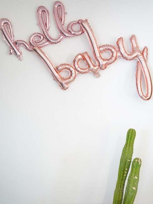 """Różowe balony ,,hello baby"""" na białej ścianie"""