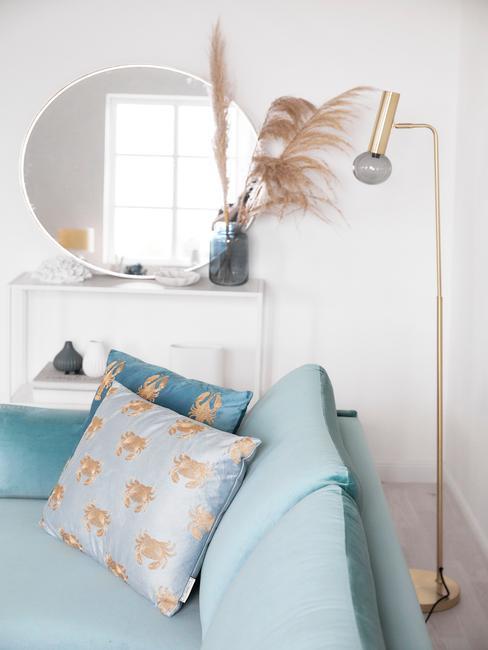 Biały salon z komodą o tym samym kolorze i turkusową sofą z poduszkami z jedwabiu