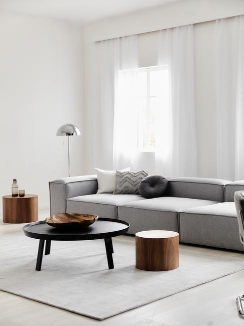 Szara, aksamitna sofa w salonie z czarnym i drewnianymi stolikami