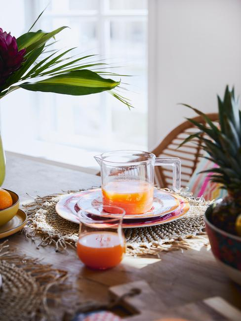 Szklany dzbanek z sokiem na kolorowych talerzykach