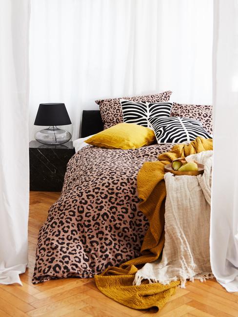 Łóżko z narzutą we wzór w panterkę oraz czarny stolik nocny