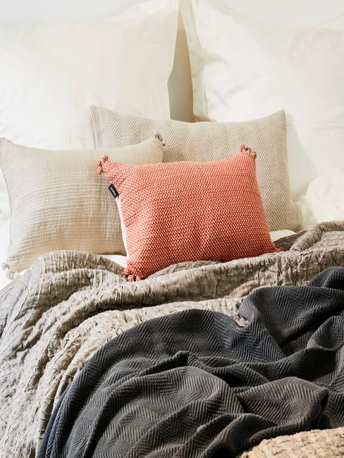 Łóżko z dwoma białymi poduszkami, dwoma beżowymi i jedną w Living Coral