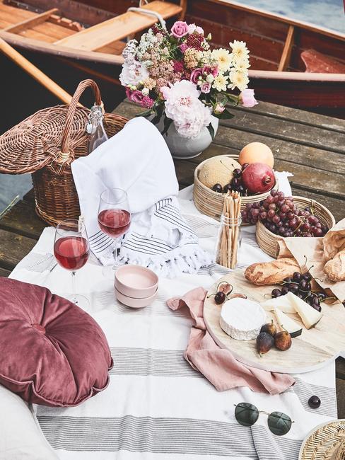 Piknik na pomoście nad jeziorem z koszem piknikowym, przekąskami i kocem do siedzenia