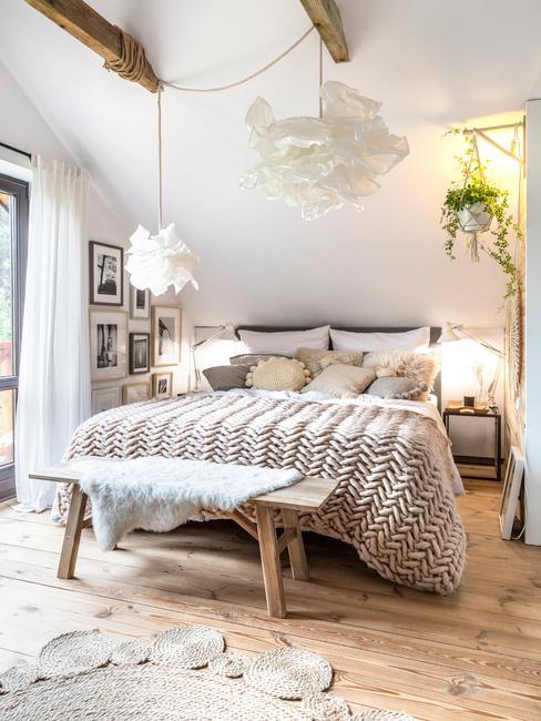 Sypialnia w stylu boho-skandi z drewnianą ławką, łożkiem z kocem i poduszkami wiszącą rośliną na poddaszu