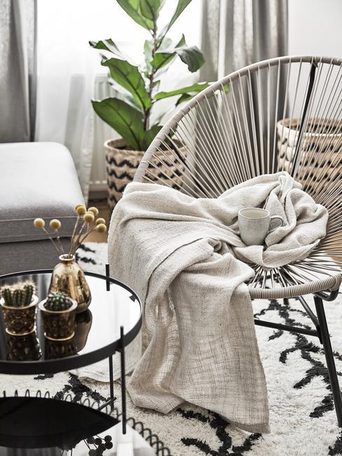 Fotel a przy nim stolik pomocniczy. W tyle okno oraz roślina doniczkowa ow ozdobnym koszu