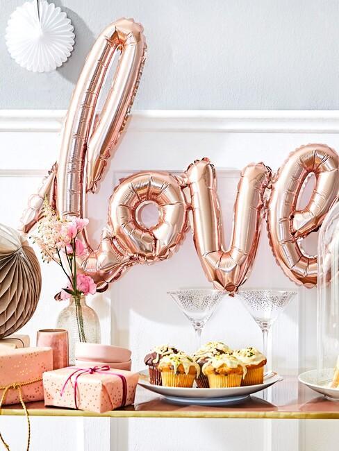 Drewniany stoliczek z deserami oraz prezentami przy białej ścianie z balonem