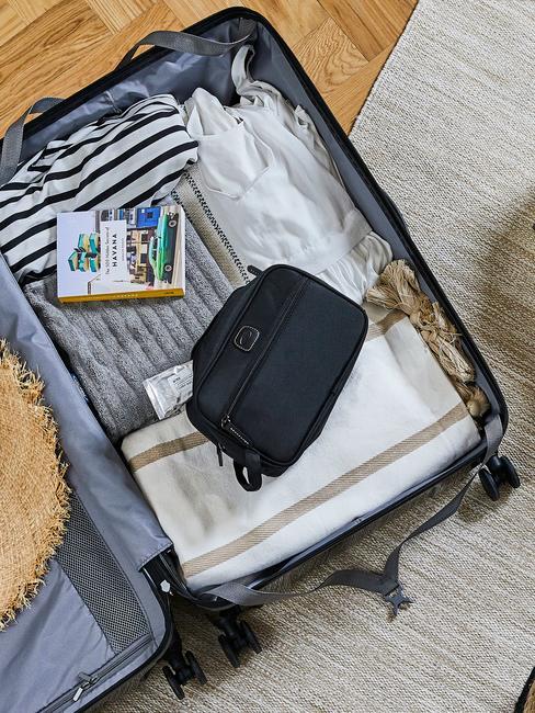 Otwarta walizka na kremowym dywanie