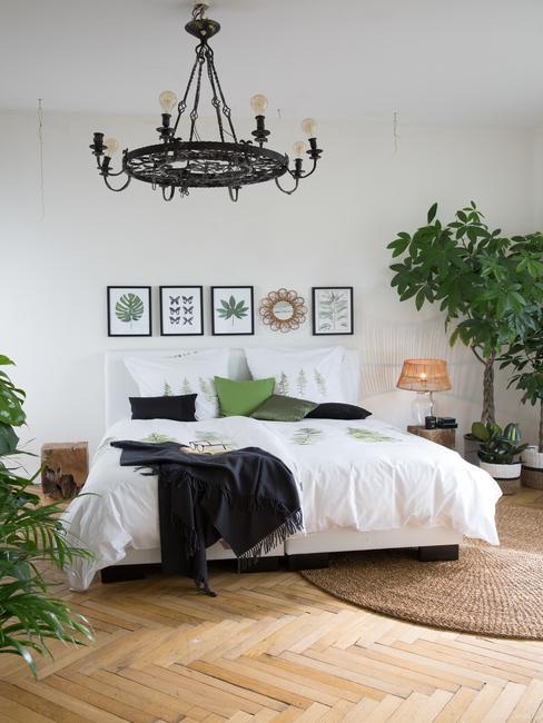 Jasna sypialnia z łóżkiem rozmiaru king size, roślinami i mosiężnym żyrandolem