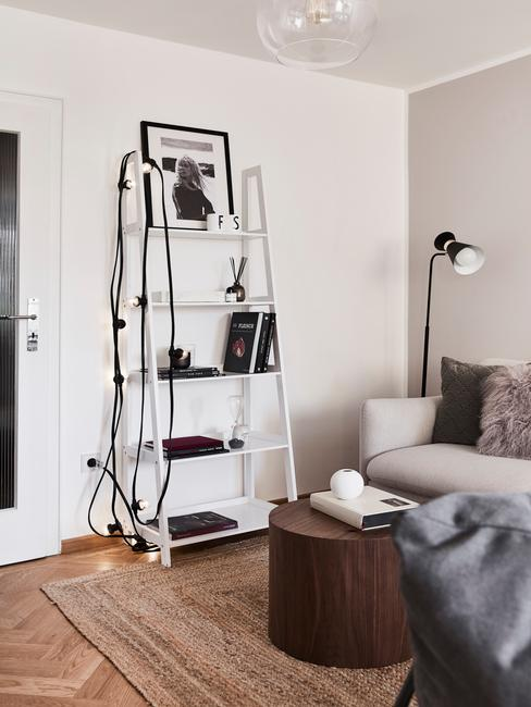 Róg salon z kremową kanapą oraz białą półką z oświetleniem i dekoracjami
