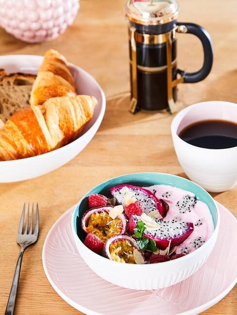 Zbliżenie na białą miseczką z muesli na różowym talerzyku, miskę do pieczyna, białą filiżankę i ekspres do kawy