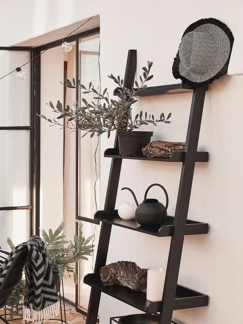 Czarna półka na balkonie z oliwką i drewnianymi dekoracjami