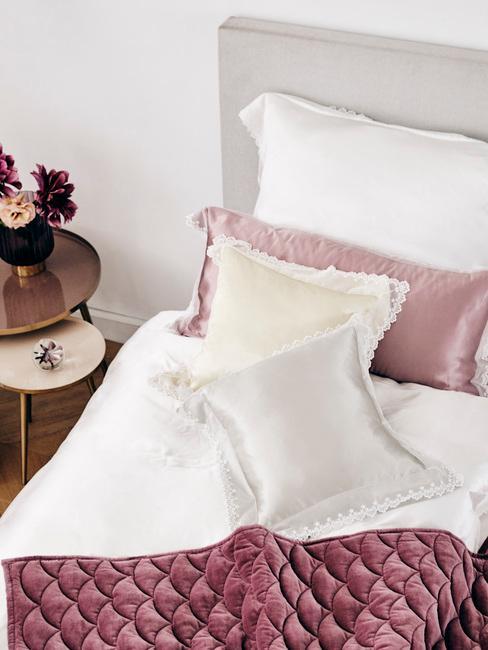 Łóżko z białą pościelą oraz poduszkami dekoracyjnymi z aksamitu