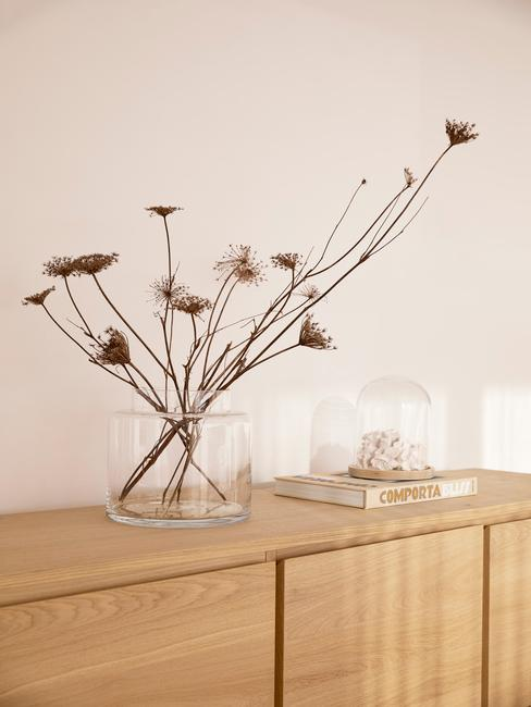 Szklany wazon z suszonymi kwiatami stojący na drewnianej komodzie