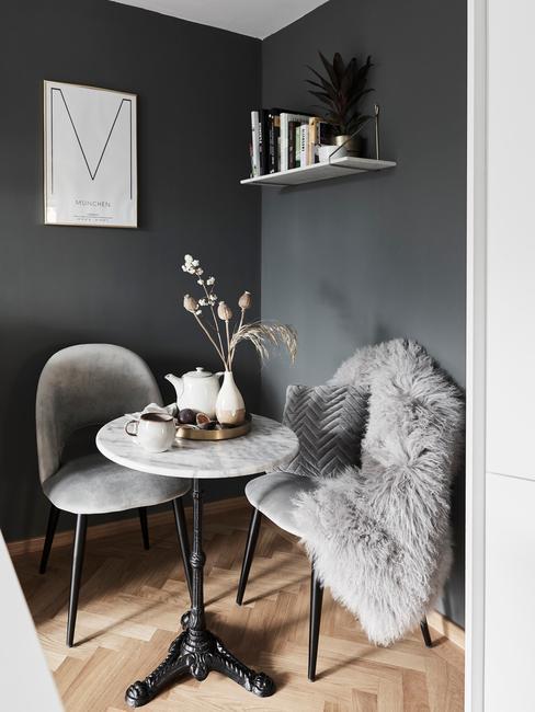 Szary szalon z dwoma, szarymi krzesłami i marmurowym stolikiem z wazonem z kwiatami i imbrykiem