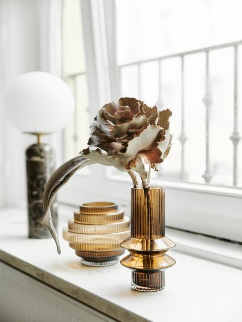 Biały parapet z lampą oraz złotym wazonem z suszonym kwiatem