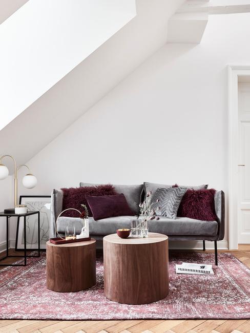 Przytulny salon na podda. Szara sofa oraz bordowy dywan.