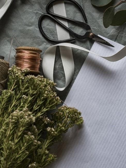 Rośliny, druciany sznubek, nożyczki oraz wstążka ułożone na blacie