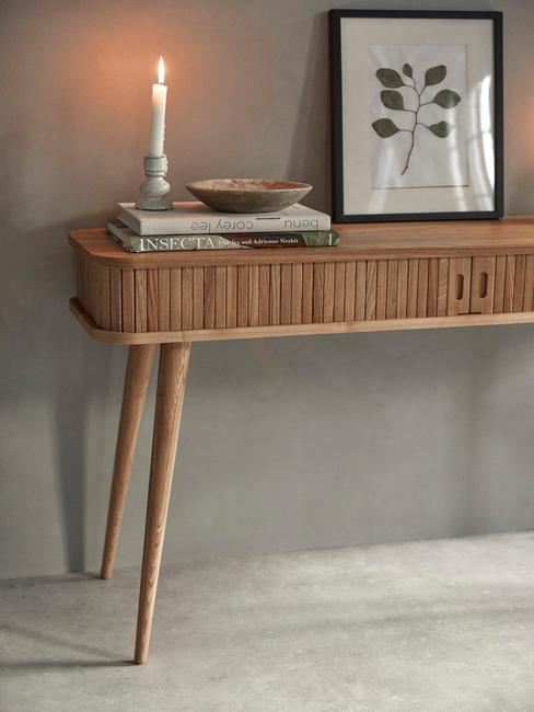 Drewiniana konsola na któej stoi zapalona świeca i grafika z motywem roślinnym