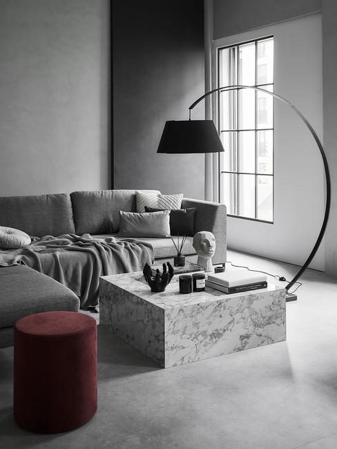 Szary salon w stylu industrialnym z marmurowym stolikiem kawowym, czarną lampą praz bordowym pufem