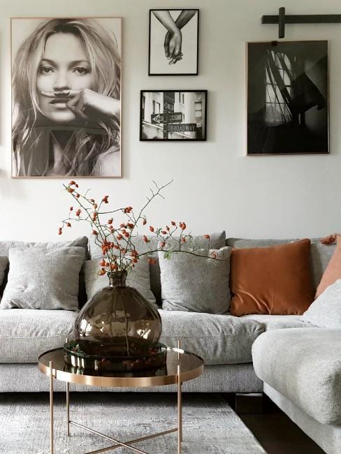 Szara sofa z rudymi poduszkami, stolik kawowy a na nim wazon z jesienną dekoracją