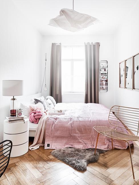 Biała sypialnia z podwójnym łożkiem i różową narzutą oraz białym stolikiem nocnym i szarymi zasłonami
