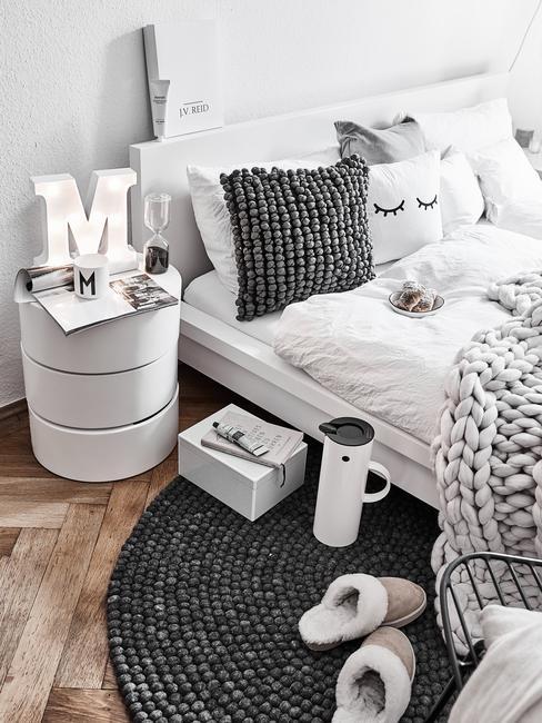 Biało - szara sypialnia w stylu skandynawskim z łóżkiem z białą pościelą i szarymi elementami dekoracyjnymi