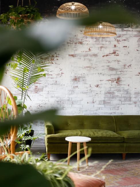 Biała, ceglana ściana w salonie z zieloną kanapą oraz roślinami